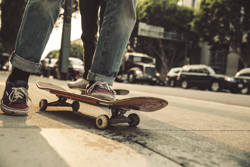 Close-up of man with skateboard on sidewalk - SUF00529
