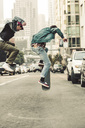 USA, California, San Francisco, two young men skating on the street - SUF00532