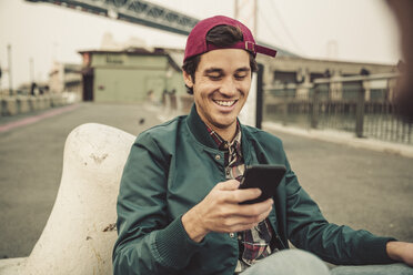 Portrait of smiling young man using cell phone - SUF00535