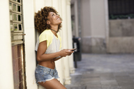 Smiling woman with afro hairstyle holding smartphone outdoors - JSMF00004