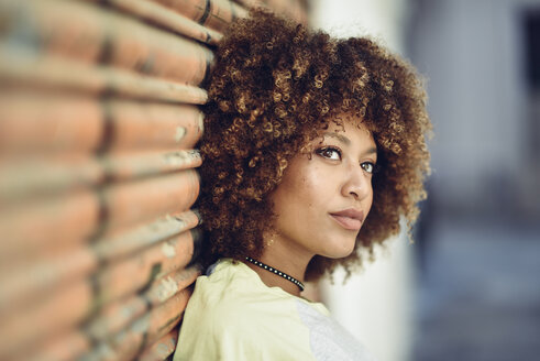 Portrait of woman with afro hairstyle leaning against roller shutter - JSMF00007