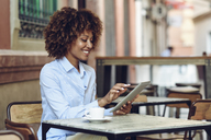 Smiling woman with afro hairstyle sitting in outdoor cafe using tablet - JSMF00013