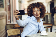 Woman with afro hairstyle sitting in outdoor cafe taking a selfie - JSMF00016