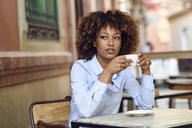 Woman with afro hairstyle sitting in outdoor cafe drinking coffee - JSMF00019