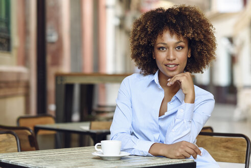 Portrait of smiling woman with afro hairstyle sitting in outdoor cafe - JSMF00022