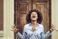 Portrait of woman with afro hairstyle screaming outdoors - JSMF00028