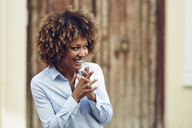 Laughing woman with afro hairstyle outdoors looking sideways - JSMF00034