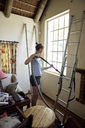 Young woman renovating her home hoovering - ECPF00182