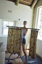 Young woman renovating her home carrying curtain rod - ECPF00185
