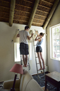 Young couple renovating their home painting the wall together - ECPF00188