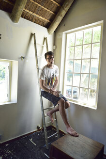 Portrait of smiling young man renovating his home - ECPF00191