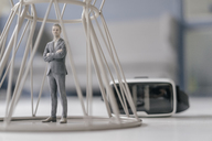 Miniature businessman figurine standing inside structure ext to VR glasses - FLAF00142