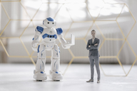 Miniature businessman figurine standing next to robot with laptop - FLAF00145