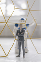 Miniature businessman figurine standing in front of robot seperated by structure - FLAF00148