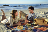 Happy couple having a picnic on the beach - ECPF00212
