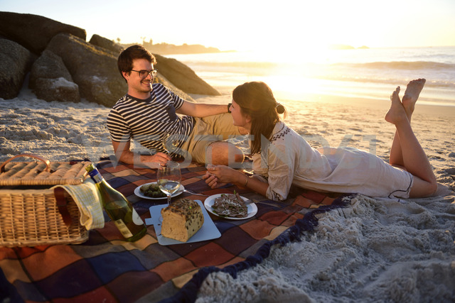 Happy couple having a picnic on the beach at sunset - ECPF00215