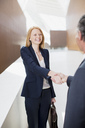 Smiling businesswoman shaking hands with businessman - CAIF01265