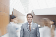 Portrait of confident businessman with co-workers rushing by in lobby - CAIF01316