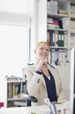 Smiling woman looking up in office - CAIF01322