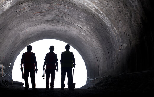 Silhouette of workers in tunnel - CAIF01325