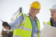 Business people in hard hats talking on site - CAIF01343