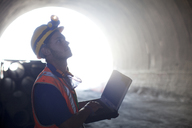 Worker using laptop in tunnel - CAIF01355