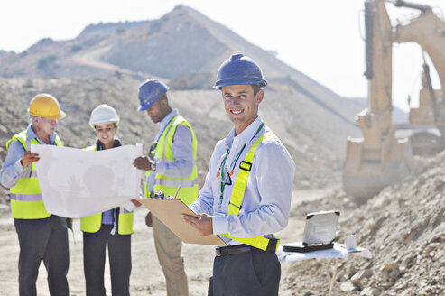 Businessmen reading blueprints in quarry - CAIF01364