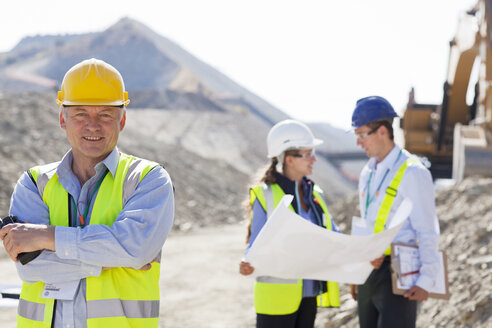 Businessman in hard hat smiling in quarry - CAIF01382