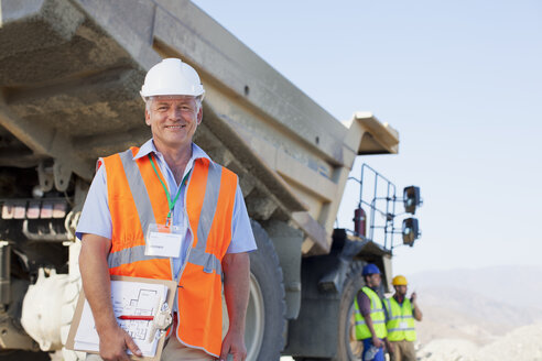 Businessman standing by truck on site - CAIF01385