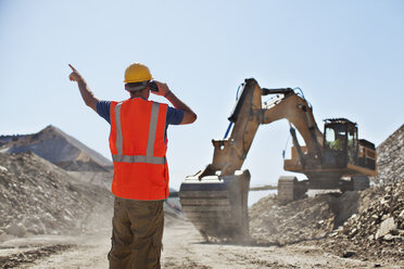 Worker directing digger in quarry - CAIF01409