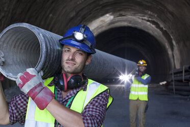 Workers carrying long pipe in tunnel - CAIF01436