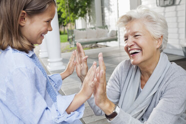 Woman and granddaughter playing clapping game - CAIF01439