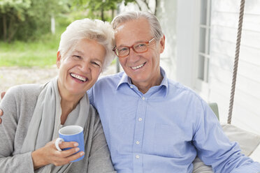 Smiling couple sitting on porch swing - CAIF01445