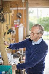 Man working in garage - CAIF01457