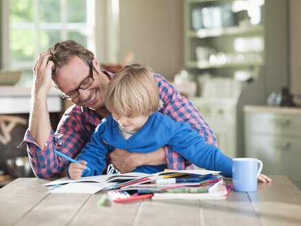Father and son doing homework at kitchen table - CAIF01475