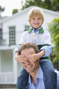 Boy covering father's eyes outdoors - CAIF01478