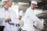 Chefs talking in restaurant kitchen - CAIF01496