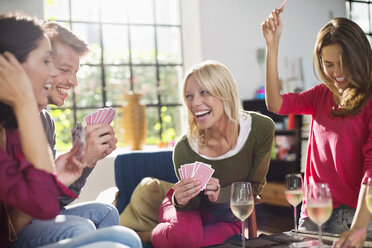 Friends playing card game in living room - CAIF01520