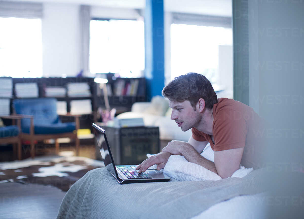 Man using laptop on bed - CAIF01523 - Paul Bradbury/Westend61