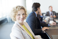 Businesswoman smiling in meeting - CAIF01595