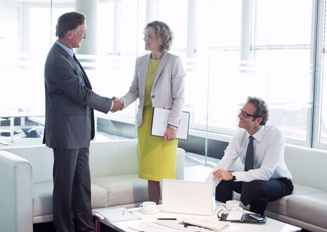 Business people shaking hands in office lobby area - CAIF01604
