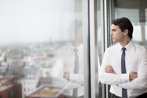 Businessman looking out office window - CAIF01616