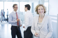 Businesswoman smiling in office hallway - CAIF01631
