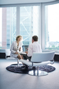 Business people talking in office lobby - CAIF01634