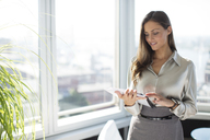 Businesswoman using digital tablet in office - CAIF01643