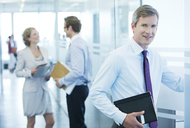 Businessman smiling in office hallway - CAIF01664