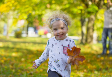 Happy little girl running with autumnal leaf in park - WWF04196
