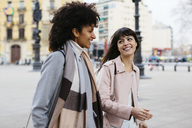 Spain, Barcelona, two happy women walking in the city - EBSF02144