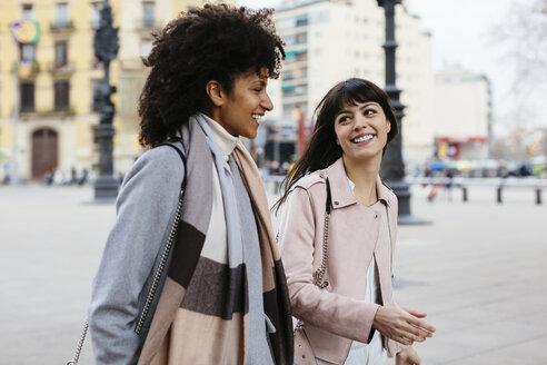 Spain, Barcelona, two happy women walking in the city - EBSF02144