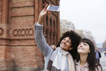 Spain, Barcelona, two happy women taking a selfie at a gate - EBSF02147